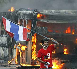 A supporter of former Thai Prime Minister Thaksin Shinawatra waves a national flag in front of a torched bus during a protest in Bangkok